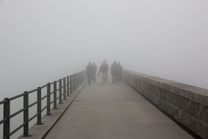 A group of climbers returning from their alpine routes walk the dam at Räterichsbodensee with clouds rolling up Grimsel Valley, Berner Oberland, Switzerland. Architecture Background Disappearing Climbers Clouds Clouds Rolling In Dam Fog Full Length Grey Grey Day Group Of People Leading Lines Masonry People Poor Visibility Returning Structures & Lines Visibility Wall