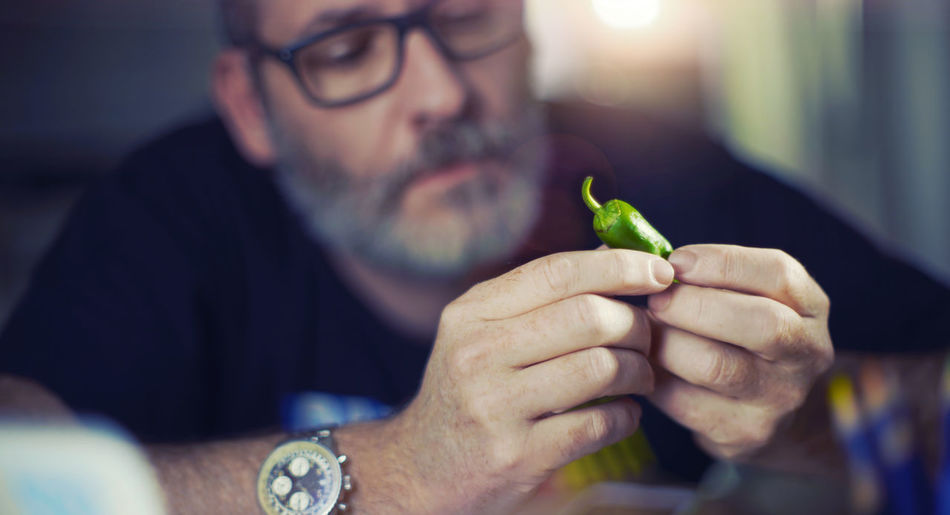 Close-up of man looking at chili pepper