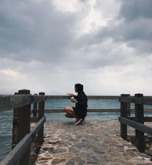 Woman Crouching On Bridge Over Sea Against Sky