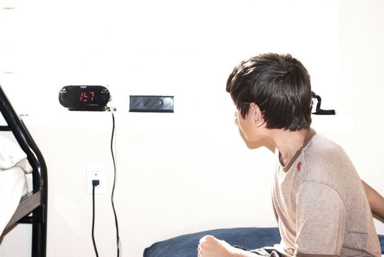 Side view of boy looking at digital clock while sitting on bed