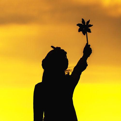 Silhouette woman against orange sky