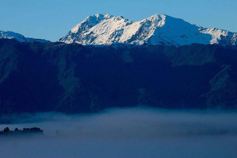 Fog over snowcapped mountain range