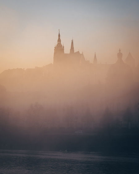 Vltava river by prague castle during foggy sunset