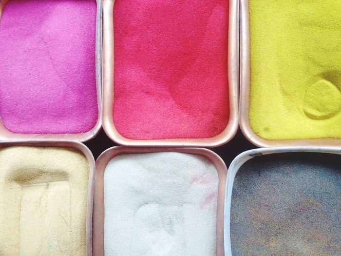 Directly above shot of colored powders at market