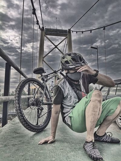 Man sitting on bicycle against sky