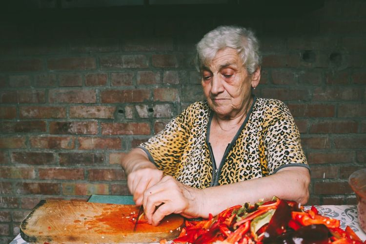 Mid adult woman holding ice cream on table against brick wall