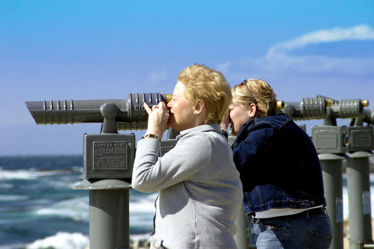 Side view of women using coin-operated binoculars against sky