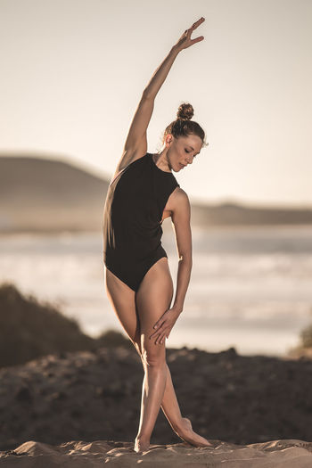 Graceful beautiful woman in yoga pose Land Beach One Person Balance Lifestyles Full Length Young Adult Leisure Activity Exercising Standing Young Women Focus On Foreground Real People Healthy Lifestyle Sea Sky Water Women Human Arm Arms Raised Skill  Yoga Woman Fraceful Copy Space