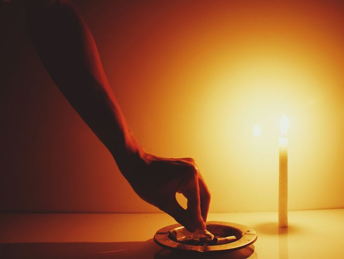 Hand extinguishing cigarette with candlelight in the night as illustration of self awareness