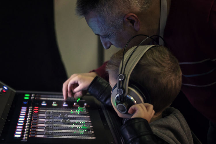 Music teacher helping boy to learn sound mixing in recording studio
