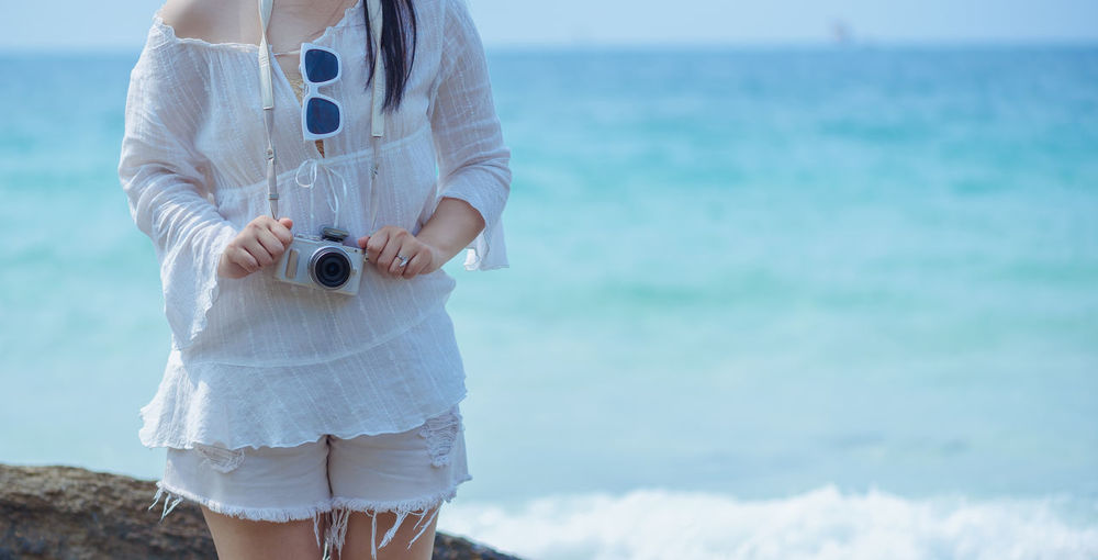Midsection Of Woman With Camera Standing Against Sea