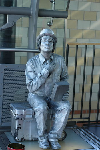 Portrait of mime painted in silver sitting on box against wall