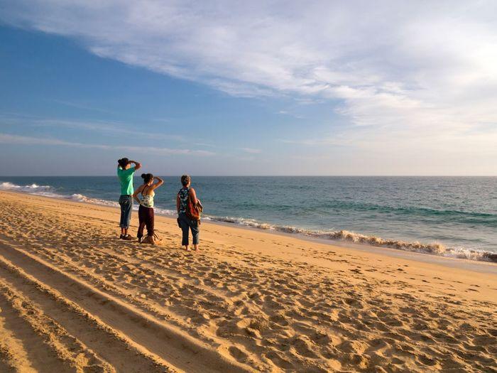 Women Standing On Sandy Beach Against Sky