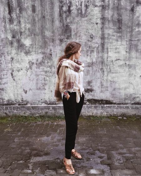 Full Length Of Young Woman Looking Away While Standing Against Wall
