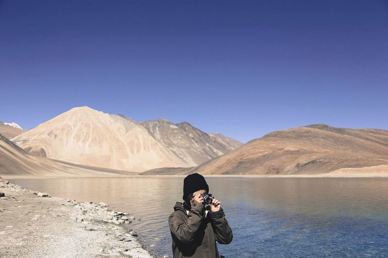 Man photographing at lakeshore against clear blue sky