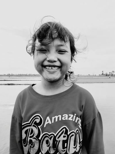 Portrait of smiling girl standing at beach