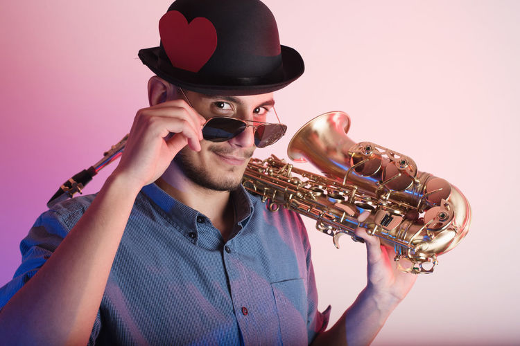 Midsection Of Man Wearing Hat Holding Saxophone