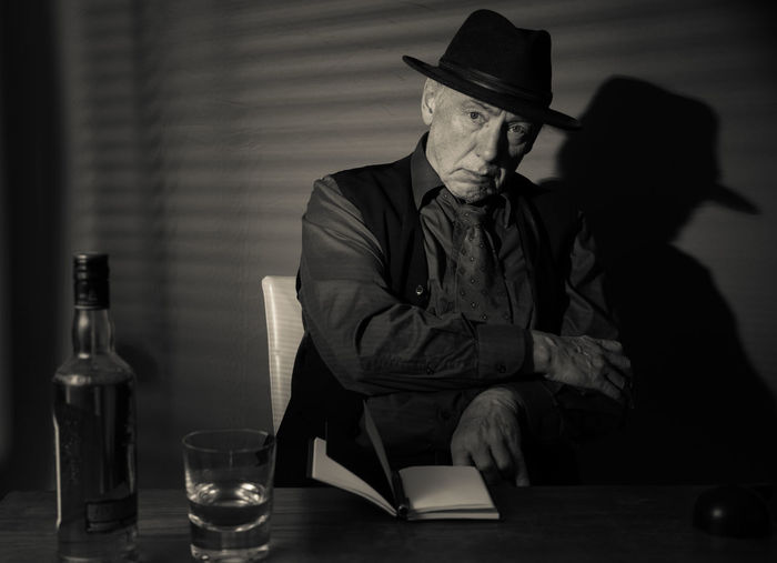 Film Noir reloaded: The dirty old detective in his bureau talking to a new client Acting Adult Hat Alcohol Bottle Day Detective Front View Hat Indoors  Mature Adult Mature Men Monochrome Old Person Old Person Sitting One Man Only One Person People Portrait Real People Sitting Studio Shot Suit Table Tie