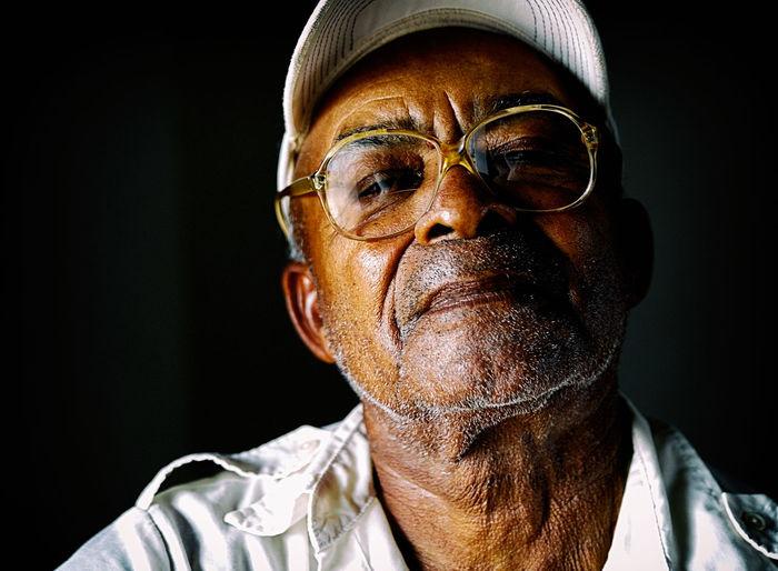 Close-up portrait of man wearing hat against black background