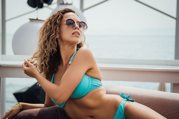 Sunglasses Sitting Young Adult Glasses Real People One Person Lifestyles Leisure Activity Fashion Young Women Swimwear Focus On Foreground Bikini Clothing Three Quarter Length Day Beauty Adult Beautiful Woman Hairstyle Hair Outdoors Contemplation Bikini Top