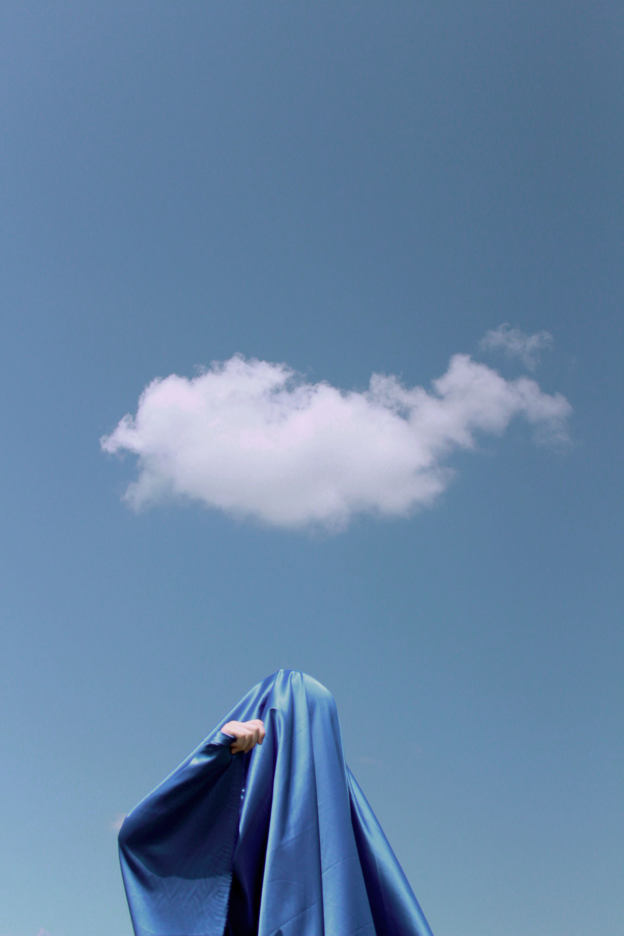 Low angle view of woman wearing scarf standing against sky