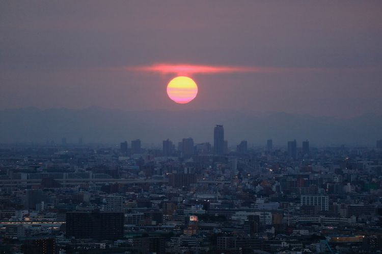 Cityscape against sun in sky during sunset