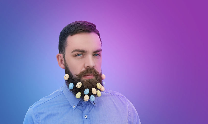 Portrait of bearded man with eatser eggs against colored background