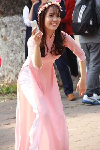 Young woman in dress holding mobile phone and dancing on street