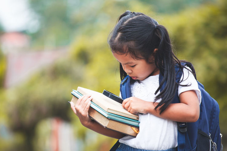 Back to school. Cute asian child girl with school bag holding books and magnifying glass ready to go to school in nature background Asian  Happy Student Adorable Assessories Back To School Backpack Bag Book Child Cute Girl Holding Kid Knowledge Learn Magnifying Glass Portrait Pupil School Smiling Study