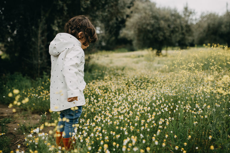 Cute girl standing on field amidst flowers