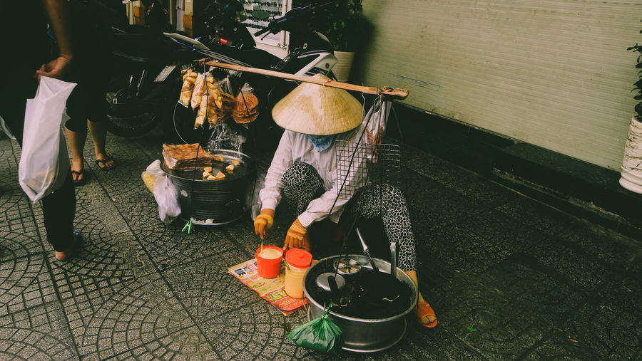 Woman wearing asian style conical hat selling food in market