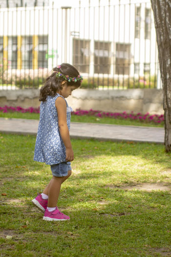 Side view of a girl standing against plants
