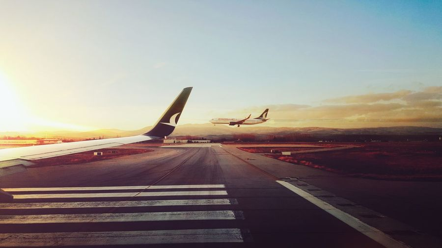 Airplane Transportation Air Vehicle Airport Runway Flying Aerospace Industry Asphalt Airport Mode Of Transport Road Sky Aircraft Wing Sunset No People Commercial Airplane Outdoors Day