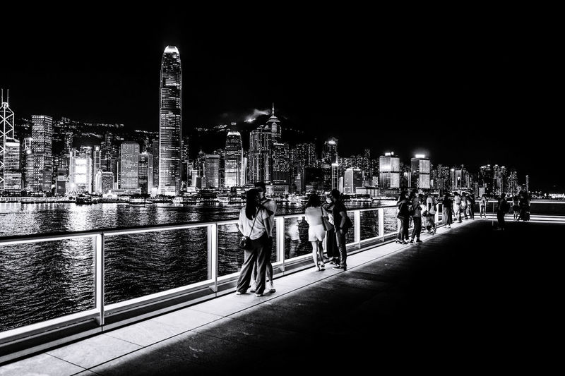 People by illuminated buildings against sky at night