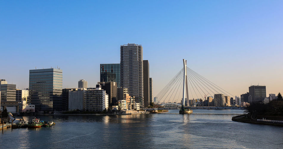 Panorama of sunset sumida river in tokyo with hanging bridge, boats and skyscrapers