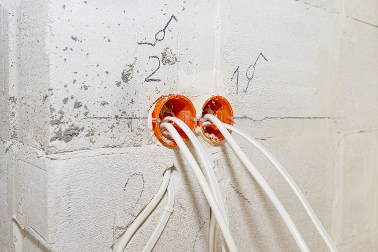 Orange, round junction box mounted in the white wall with protruding electric cables.