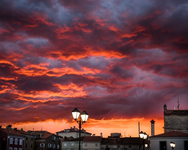 Silhouette Of Cityscape Against Dramatic Sky