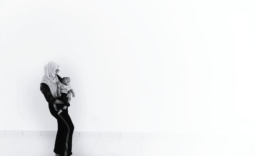 Mother carrying daughter while standing against white background