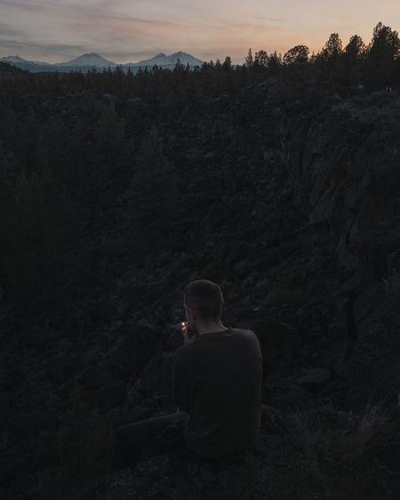 Rear view of man smoking cigarette at mountain
