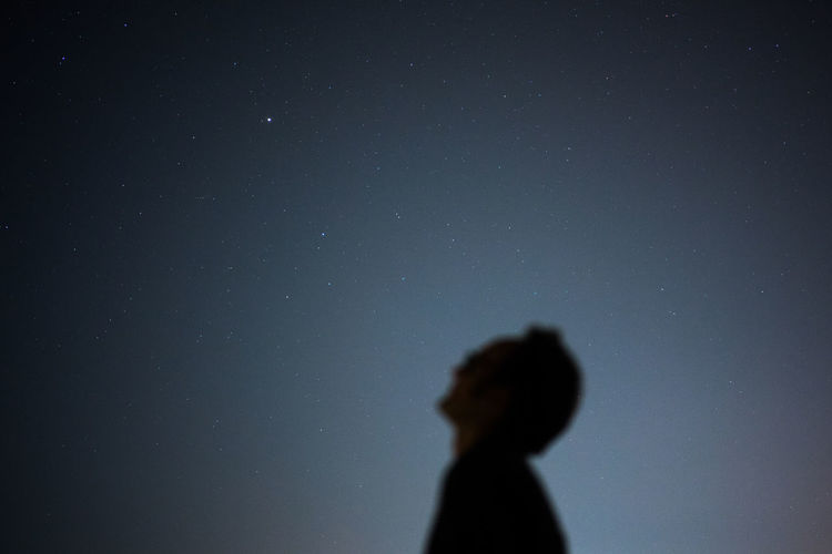 Low angle view of man with head back standing against sky at night