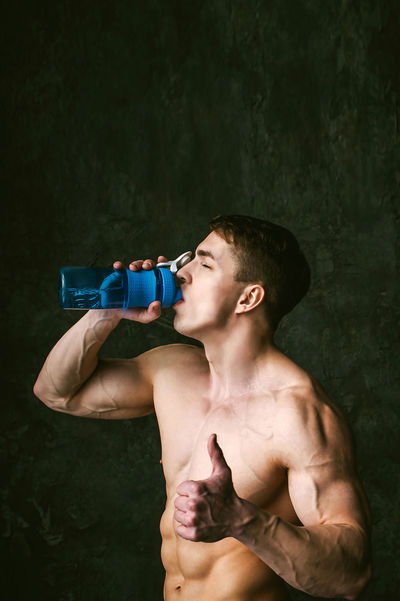 Adult Day Drink Drinking Food And Drink Holding Leisure Activity Lifestyles Muscular Build One Person Outdoors People Real People Refreshment Shirtless Standing Waist Up Water Water Bottle  Young Adult Young Men