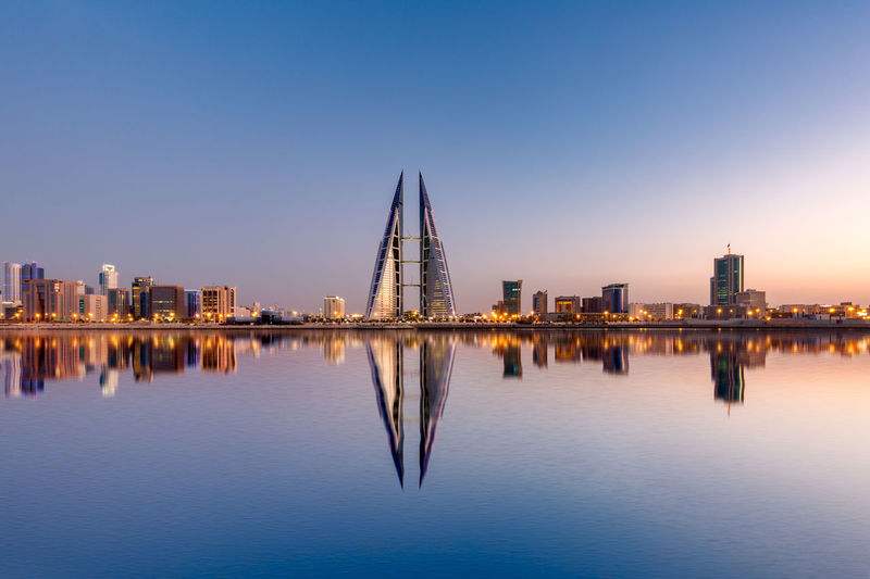 Reflection of illuminated buildings in water against bahrain skyline
