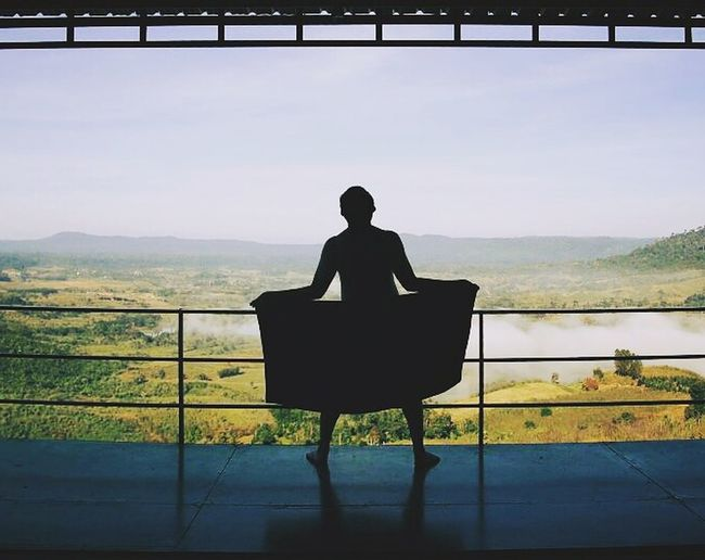Rear view of a silhouette man sitting outdoors