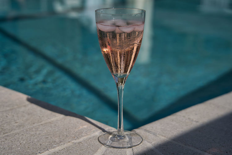 Close-up of wine champagne glass on pool
