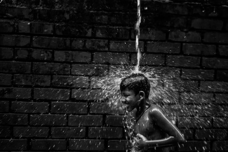 The Street Photographer - 2018 EyeEm Awards Architecture Boys Brick Brick Wall Child Childhood Leisure Activity Lifestyles Males  Men Motion One Person Outdoors Real People Shirtless Wall Wall - Building Feature Water Wet Wet Hair 2018 In One Photograph