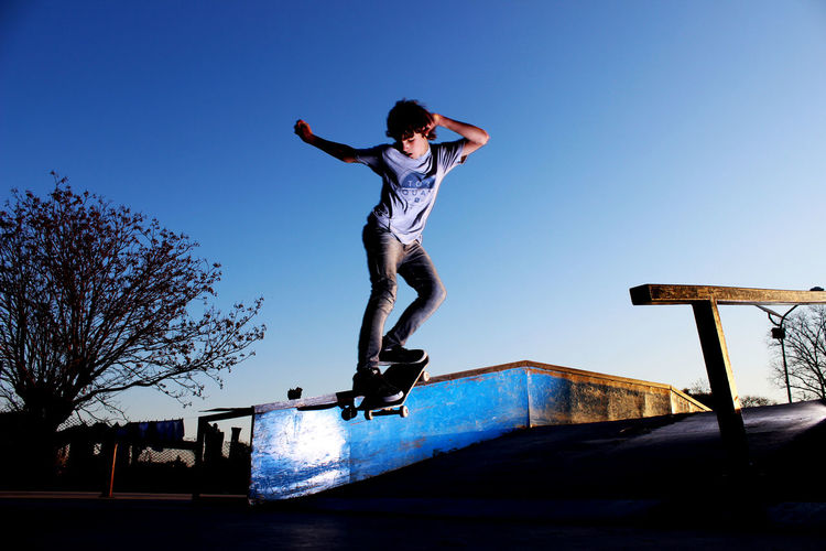 Full length of boy skateboarding against clear blue sky during sunset