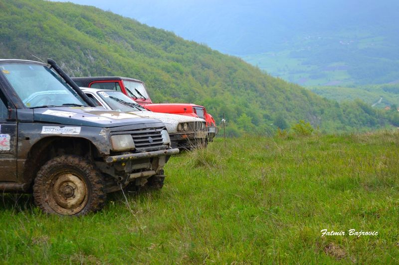 Posing Beauty In Nature Field Grass Grassy Green Green Color Hill Jeeps Land Vehicle Landscape Mode Of Transport Mountain Mountain Range No People Remote Scenics Stationary Tranquil Scene