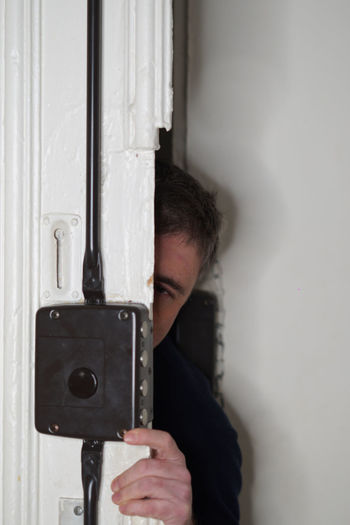 Portrait of burglar hiding behind door