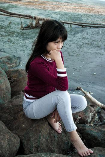 Full length of girl sitting on rock by river
