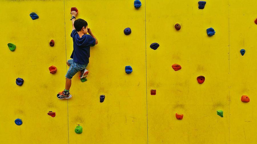 Rear view full length of boy climbing wall